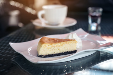 A piece of cheese cake and whipped cream in white plate with coffee cup on table in cafe