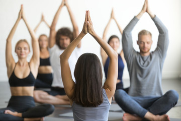 Group of young sporty people practicing yoga lesson with instructor, sitting in Sukhasana exercise, Easy Seat pose, working out, students training in club, indoor, studio. Wellness and wellbeing