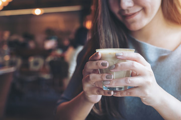 Closeup image of Asian woman holding and drinking hot coffee with feeling good in cafe