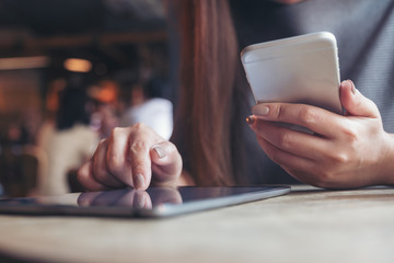 Closeup image of a woman's hand pointing and touching tablet pc while using mobile phone in cafe