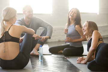 Group of young sporty people sitting in circle having a break. Friends laughing with joy, feeling excited about training, sitting on the floor, feeling fatigued but nice after good exercising