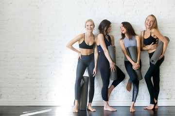 Group of young sporty girls with yoga mats standing at white wall. Female companions in gym resting after fitness, indoor full length, loft studio, copy space Wall mural