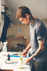 A young guy, a tattoo artist preparing for the session, prepares the tools and ink for tattoo