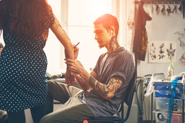 A young guy, a tattoo artist preparing for the session, draws a sketch on the body of the client in a welcoming environment
