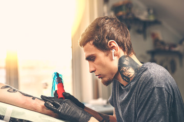 A young guy, beats a tattoo on the hand of the girl in a tattoo parlor, rotary tattoo machine, black ink, lens flare