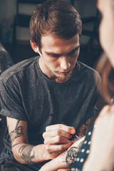 A young guy, a tattoo artist preparing for the session, draws a sketch on the body of the client