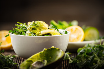 Preparation of avocados in green salad/Preparation of avocados in green salad. Vegetables and a bottle of olive oil.