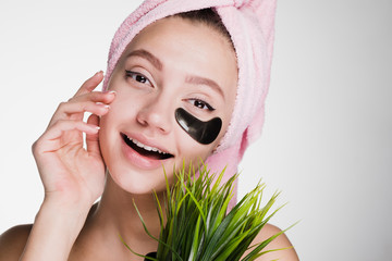 happy woman with a towel on her head after the shower apply patches under the eyes