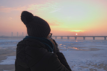 A girl in a brown jacket and brown woolen hat with big pompon drinks take-out coffee and watches the sunrise in Kyiv, Ukraine. Winter morning landscape