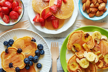 Top view of assorted pancakes with strawberry, blueberry, banana, honey and nuts. Breakfast for 3 person.