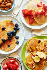 Top view of homemade pancakes with fresh fruits and nuts on kitchen table. Family breakfast concept.