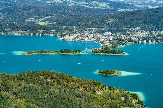 Wörthersee in Österreich Kärnten mit der Kapuzinerinsel (mittig) und dem Ort Pörtschach im Hintergrund sowie der Schlangeninsel links