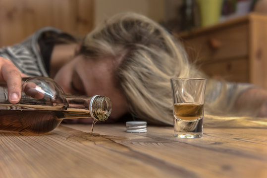 A woman (25-30) fell asleep drunk at the table. Alcohol runs out of a brandy bottle. Concept: alcohol abuse or drinking