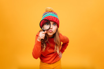 Joyful Young girl in sweater and hat looking at camera