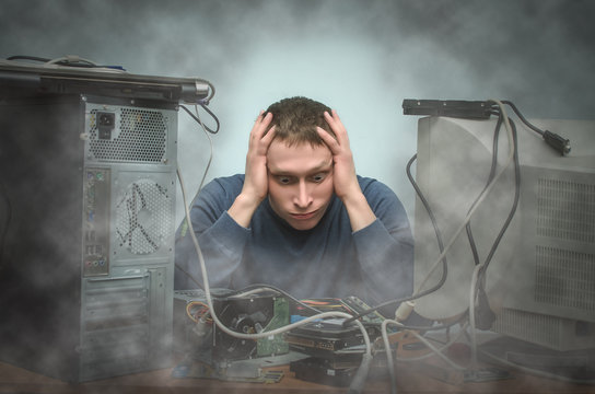 Tired and bored computer repairman is sitting on his workplace in smoke of burning hardware. Computer technician tired from his work and users. PC repair service center.