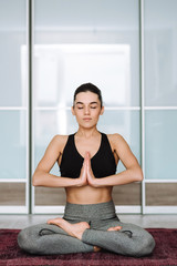 Beautiful brunette girl sitting in lotus pose. The model practices yoga in a bright room.