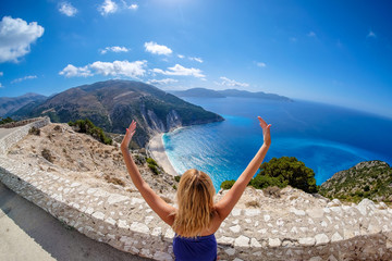 Woman tourist looking at Myrtos Beach in Cephalonia Island Greece from above