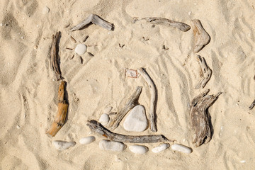 Artistic Sand drawings on the beach with pebbles and .wooden sticks. Zen activities at the beach