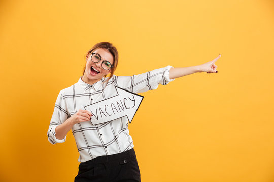 Portrait of funny woman in plaid shirt holding speech arrow pointer with word vacancy isolated over yellow background