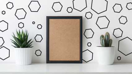 Modern room decoration. Various cactus and succulent plants in different pots. Mock-up with a black frame. Scandinavian home decor.
