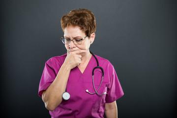 Portrait of senior lady doctor making thinking gesture