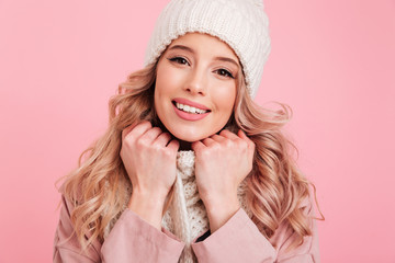 Portrait of happy elegant woman 20s dressed in warm knitted hat and scarf posing on camera with smile, isolated over pink background