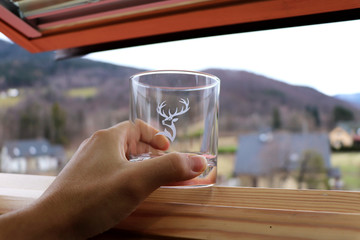 A glass of whiskey in hand and view on countryside