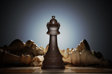 Victory in chess. Queen in front and many dead pieces in background. 3D rendered illustration.