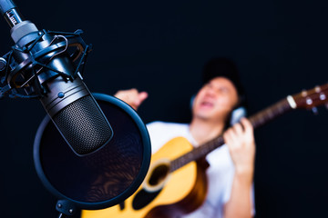 asian male musician playing acoustic guitar in recording studio, focus on microphone