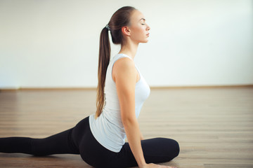 woman practicing yoga pose at yoga healthy sport gym, girl stretching her legs