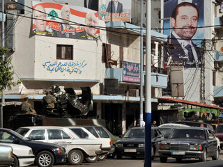 Lebanese army soldiers sit on their military vehicle in the al-Tabbaneh district of Tripoli