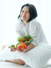 Young Asian woman with salad on white background