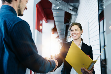Two business people shaking hands after meeting. Finishing successful transaction with signed papers