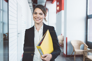 Portrait of smart casual dressed beautiful woman with paperwork standing in the office