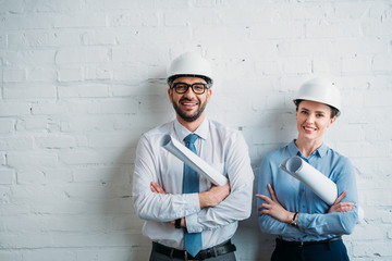 happy architects in hard hats standing in front of white brick wall with blueprints