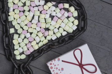 heart shape arranged marshmallows with metal chain. love concept on wood background