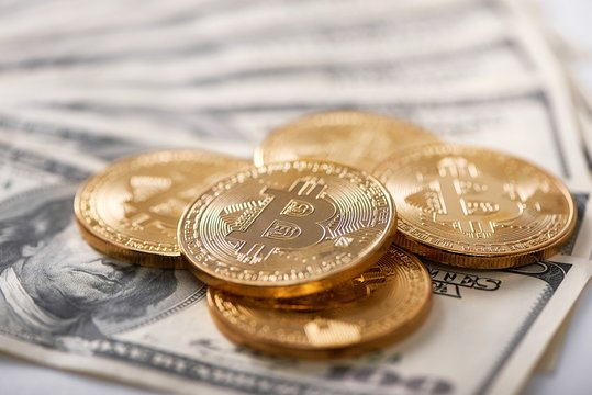 New over old. Stack of golden encrypted bitcoins lying on dollar banknotes presenting new futuristic digital currency. Cryptocurrency virtual web electronic money blockchain exchange banking finance