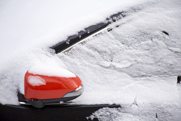 Covered by snow black car with red side mirror