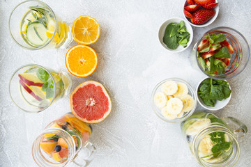 Glasses of detox water with sliced fruit, vegetables, berries and herbs and bowls with ingredients: strawberry, mint, spinach, grapefruit on a light stone background, top view