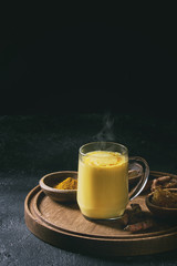 Cup of ayurvedic drink golden milk turmeric latte with curcuma powder on round wooden tray and ingredients above over black texture background. Copy space. Toned image