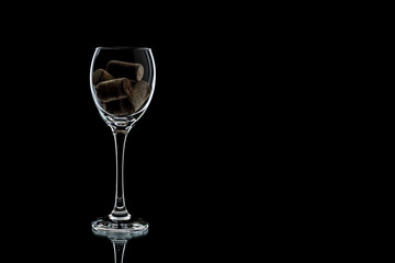 a glass of wine with cork inside completely. the glass is on a black background (isolate).