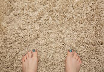 Woman feet standing on beige carpet in bathroom