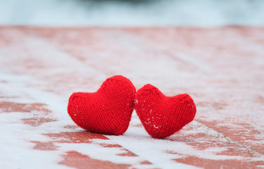 the symbol of love two red warm knitted hearts lie together on a wooden table