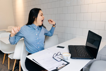 tired woman sitting in the office at the table and yawning