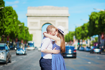 Couple kissing in front of Triumphal arch in Paris