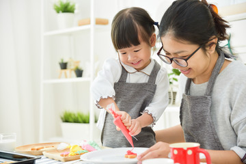 Asian Kid and young mother decorating cookies.