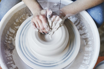 Ceramic studio, craft working process with clay potter's wheel, close-up of hands doing object