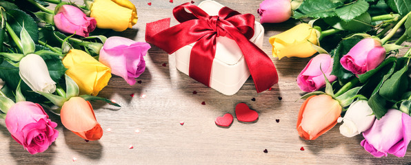 Bouquet of multicolor roses with decorative heart and presents. St Valentine's concept