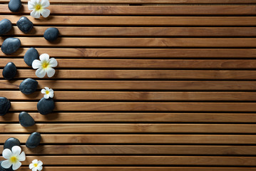 black massage pebbles and spa flowers set on wooden board