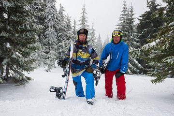 Happy snowboarders relax on the mountain slope